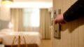 Mand åbner dør til hotelværelse