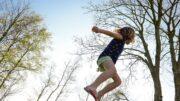 Pige hopper på trampolin udenfor om aftenen