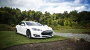 Tesla holder parkeret på græsplæne udenfor